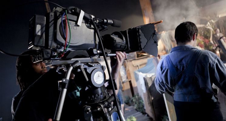 A film studio setting with a large video camera and camera operators