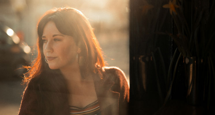 Musician Annie Drury stands on the other side of a window bathed in golden sunlight looking into the distance