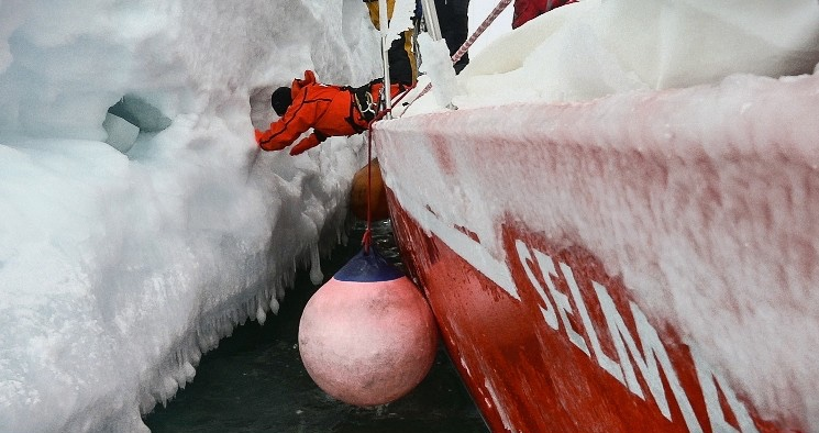 person pushing away an iceberg from a ship