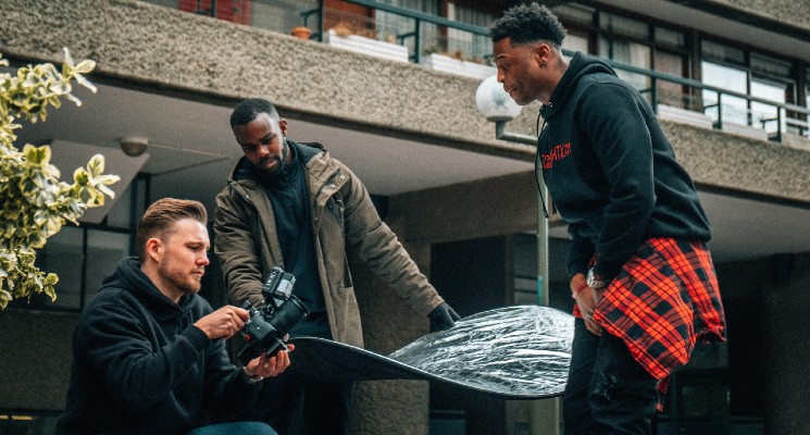 three people shooting a youtube video outside a block of flats