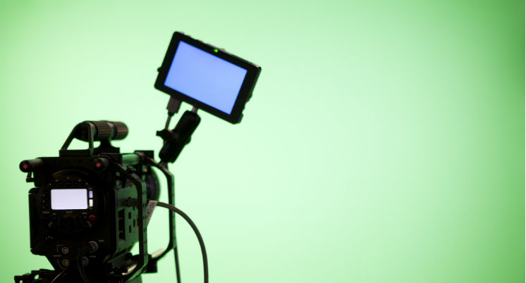 A green screen with video recording camera