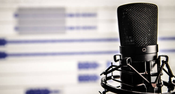 Microphone close up with recording software blurred in the background on a screen