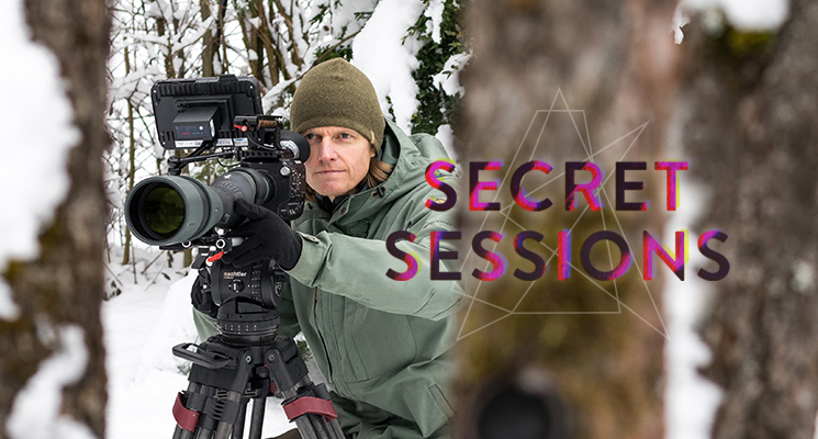Photographer Mario Kreuzer shoots video in a wooded area in the snow wearing a green jacket and hat.