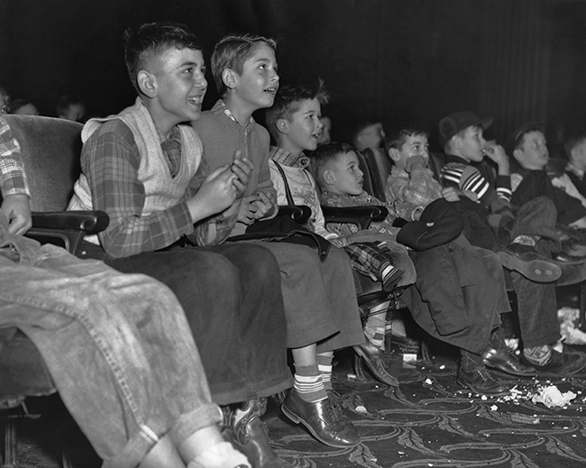 Happy children looking animated as they watch a film at the cinema