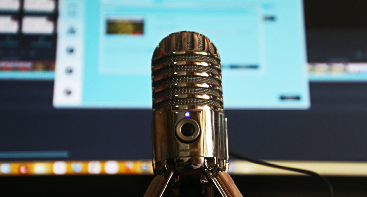 up close shot of mic in front of computer podcast recording