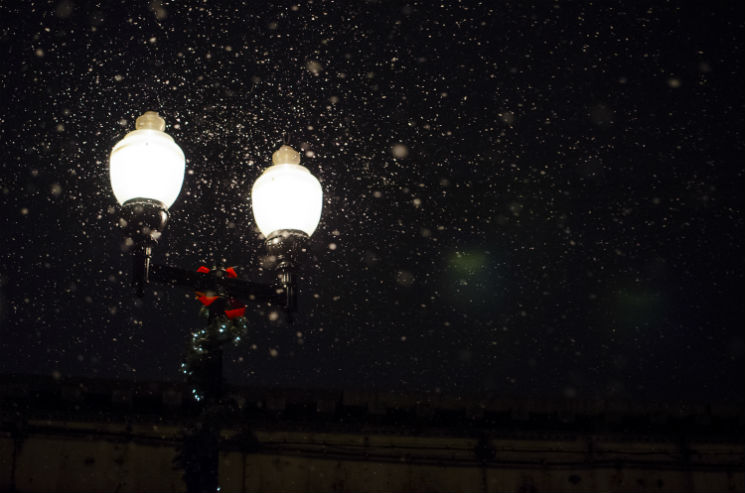 Old fashioned street lights illuminate a dark and snowy backdrop